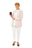 Äldre elegant kvinna för leende som rymmer den pappers- koppen Arkivbild