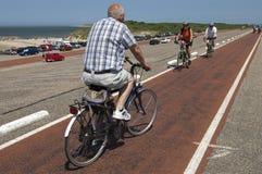 Äldre folk som cyklar på Brouwersdam, Nederländerna Arkivbilder