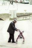 Äldre gå luta på en liten servicevagn Arkivbild