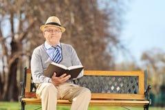 Äldre gentleman med boken som poserar på en bänk Arkivfoton