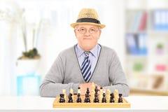 Äldre gentleman som poserar bak en schackbräde Royaltyfria Foton