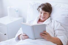 Äldre grå kvinna i den vita badrocken som sitter i sjukhussäng och läsebok arkivbilder