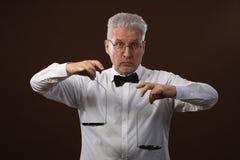 Äldre gråhårig man50-tal, i den vita skjortan, exponeringsglas och flugan som väger något på våg med kettlebells royaltyfri foto