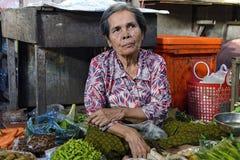 Äldre grönsakförsäljare i rysk marknad i Phnom Penh, Cambodja Arkivfoto