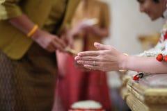 Äldre händer som häller välsignelsevatten in i handen av bruden Arkivfoton