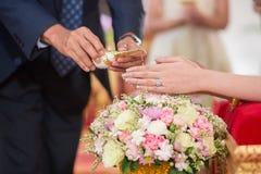 Äldre händer som häller välsignelsevatten in i handen av bruden Arkivbild