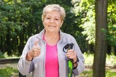 Äldre hög kvinna som rymmer nordiska gå pinnar och visar upp tummar Arkivbilder