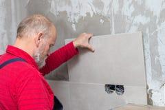 Äldre hantverkare som arbetar med tegelplattor royaltyfria foton