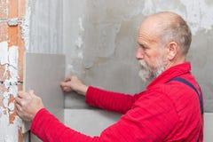 Äldre hantverkare som arbetar med tegelplattor arkivfoto