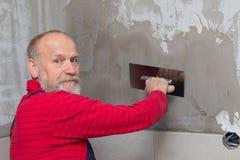 Äldre hantverkare som arbetar med tegelplattor royaltyfri fotografi