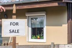 Äldre hus med tecknet 'som är till salu 'som ett tecken av försäljningen arkivfoto