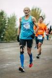 Äldre idrottsman nen framåt av mer ung löpare Royaltyfria Bilder