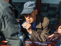 Äldre kinesiska män som spelar kort i en parkera i Peking Royaltyfri Foto