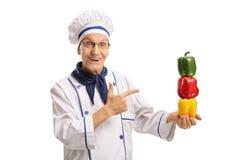 Äldre kock med att peka för peppar Arkivbilder