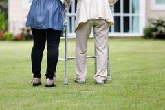 Äldre kvinnaövning som går i trädgård Royaltyfri Fotografi