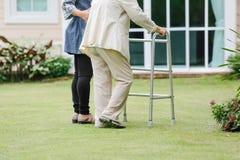 Äldre kvinnaövning som går i trädgård Arkivbilder