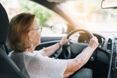 Äldre kvinna bak styrninghjulet Arkivbilder