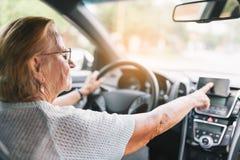 Äldre kvinna bak styrninghjulet genom att använda hennes satnav Royaltyfri Foto