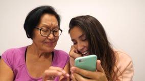 Äldre kvinna för blandat lopp och ung le dotter som hemma använder moderna grejer 4K arkivfilmer