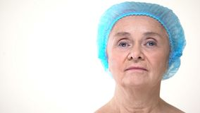 Äldre kvinna i det hygieniska locket för cosmetologytillvägagångssätt, plastikkirurgi royaltyfri foto