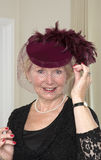 Äldre kvinna i en hatt med en skyla Arkivfoton