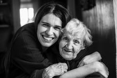 Äldre kvinna i en omfamning med hans vuxna dotter Förälskelse arkivbild
