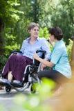 Äldre kvinna i en rullstol med en sjuksköterska Royaltyfria Foton