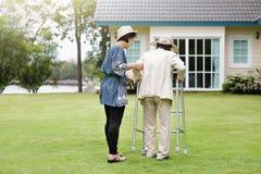 Äldre kvinna i sjukgymnastik som går i trädgård Royaltyfria Bilder