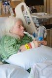 Äldre kvinna i sjukhussäng genom att använda incitamentspirometeren royaltyfri bild