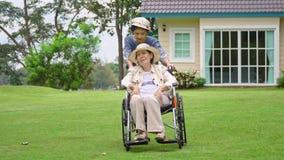Äldre kvinna i trädgård med dottern arkivfilmer