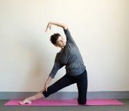Äldre kvinna i yogasidoelasticitet Arkivbild