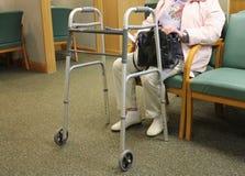 Äldre kvinna med att gå hjälpmedlet Arkivbild