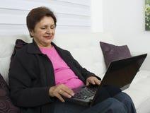 Äldre kvinna med bärbar datordatoren Royaltyfria Bilder