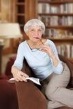 Äldre kvinna med boken och exponeringsglas som sitter i en stol Royaltyfri Bild