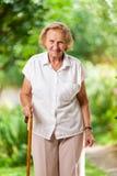 Äldre kvinna med en gå pinne Fotografering för Bildbyråer