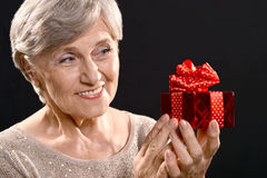 Äldre kvinna med en gåva Arkivfoto