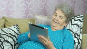 Äldre kvinna med en minnestavladator arkivfilmer