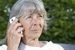 Äldre kvinna med en mobiltelefon Arkivfoto