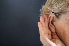 Äldre kvinna med hörapparat på grå bakgrund Conc dövhet arkivbild