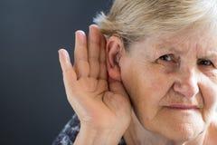 Äldre kvinna med hörapparat på grå bakgrund Släkt H för ålder arkivfoton