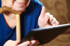 Äldre kvinna med minnestavladatoren Royaltyfri Bild