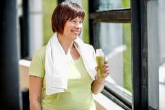 Äldre kvinna med smoothien inomhus royaltyfria bilder