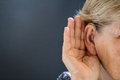 Äldre kvinna med utfrågningförlust på grå bakgrund Släkt ålder fotografering för bildbyråer