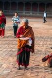 Äldre kvinna - Newar brådska som gör en puja för religiös ritual Arkivfoton