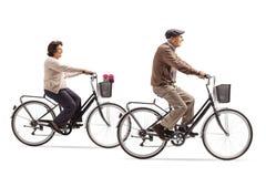 Äldre kvinna och äldre cyklar för en manridning arkivfoton