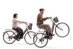 Äldre kvinna och äldre cyklar för en manridning med elderlen royaltyfria bilder