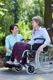 Äldre kvinna och en sjuksköterska som tillsammans ler Arkivfoto