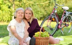 Äldre kvinna och ung kvinna på picknicken Fotografering för Bildbyråer