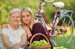 Äldre kvinna och ung kvinna på picknicken Royaltyfria Foton
