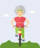 Äldre kvinna på en cykel Arkivfoton